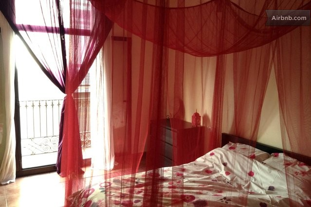 Our romantic bedroom with red netting and twinkle lights.